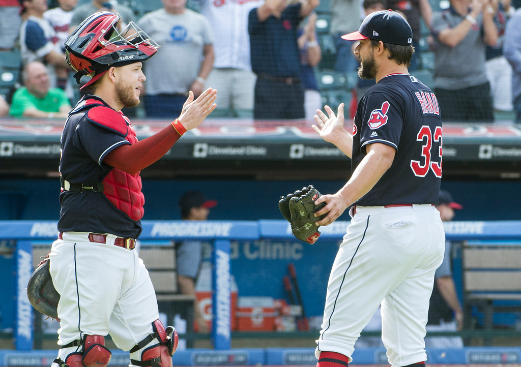 . Cleveland Indians catcher Roberto Pereza greets relief pitcher Brad Hand (33) after they defeated the Minnesota Twins 5-3 at a baseball game in Cleveland, Thursday, Aug. 30, 2018. (AP Photo/Phil Long)