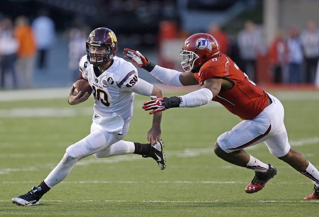 . Arizona State quarterback Taylor Kelly (10) eludes Utah defensive end Nate Orchard (8) in the fourth quarter during an NCAA college football game Saturday, Nov. 9, 2013, in Salt Lake City. Arizona State won 20-19. (AP Photo/Rick Bowmer)