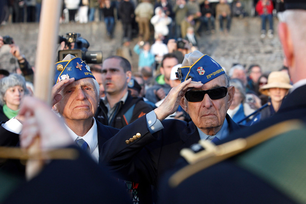 . World War II veterans of the U.S. 29th Infantry Division, Hal Baumgarten, right, 90, of Pennsylvania, and Steve Melnikoff, 94, of Maryland, salute during a D-Day commemoration, on Omaha Beach in Vierville sur Mer, western France , Friday June 6, 2014. Veterans and Normandy residents are paying tribute to the thousands who gave their lives in the D-Day invasion of Nazi-occupied France 70 years ago. (AP Photo/Thibault Camus)