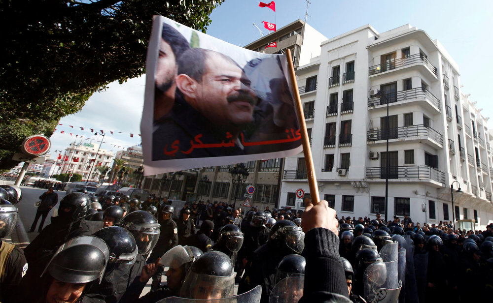. Tunisian protesters shout slogans during a demonstration after the death of Tunisian opposition leader Chokri Belaid (pictured on flag), outside the Interior ministry in Tunis February 6, 2013. Tunisia\'s secular opposition Popular Front said it was pulling out of the constituent assembly charged with writing a constitution after an opposition politician was killed on Wednesday.   REUTERS/Anis Mili