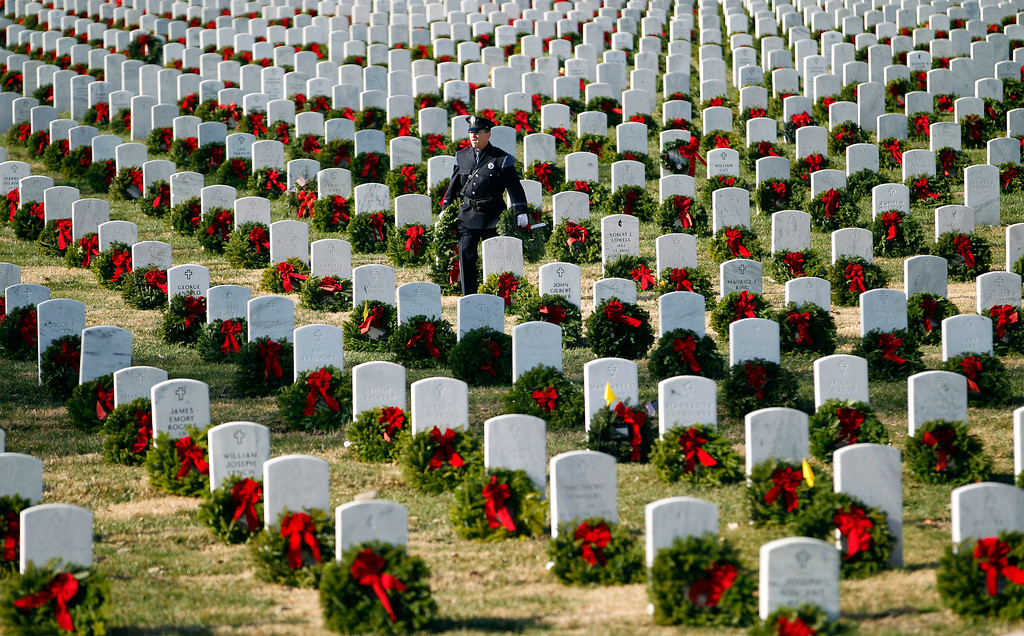 . Police officer Terry Fitzgerald of Portland, Maine, carries wreaths as he helps lay holiday wreaths at graves at Arlington National Cemetery in Arlington, Va., Saturday Dec. 15, 2012, during Wreaths Across America Day. Wreaths Across America was started in 1992 at Arlington National Cemetery by Maine businessman Morrill Worcester and has expanded to hundreds of veterans\' cemeteries and other locations in all 50 states and beyond. (AP Photo/Jose Luis Magana)