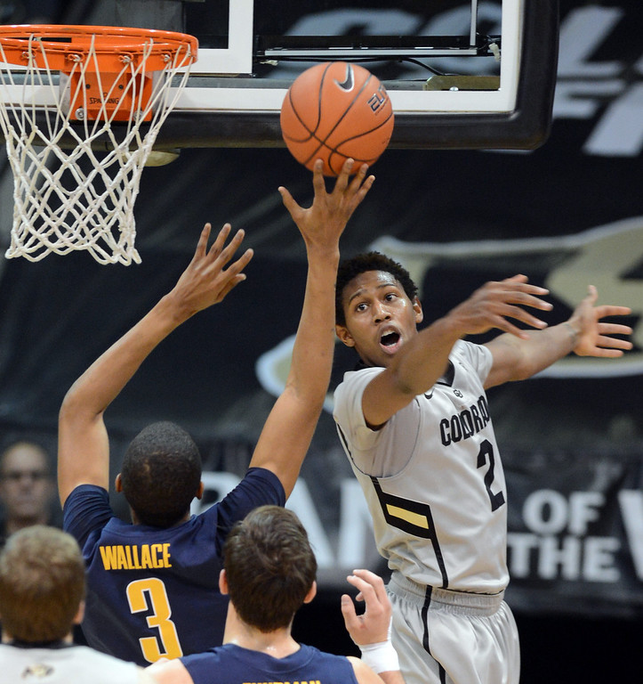 . Xavier Johnson of CU tries to block the shot of Tyrone Wallace of Cal during the first half of the January 27th, 2013 game in Boulder. Cliff Grassmick/The Daily Camera
