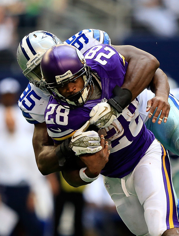 . Running back Adrian Peterson #28 of the Minnesota Vikings carries the ball as he is tackled by defensive end Caesar Rayford #95 of the Dallas Cowboys during the game at Cowboys Stadium on November 3, 2013 in Arlington, Texas.  (Photo by Jamie Squire/Getty Images)