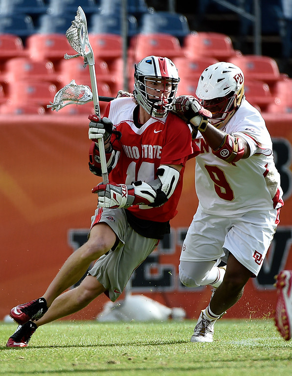 . Carter Brown (14) of the Ohio State Buckeyes is defended by  Trevor Baptiste (9) of the Denver Pioneers during the first half of their NCAA tournament quarterfinal match. The Denver Pioneers played the Ohio State Buckeyes at Sports Authority field at Mile High on Saturday, May 16, 2015. (Photo by AAron Ontiveroz/The Denver Post)