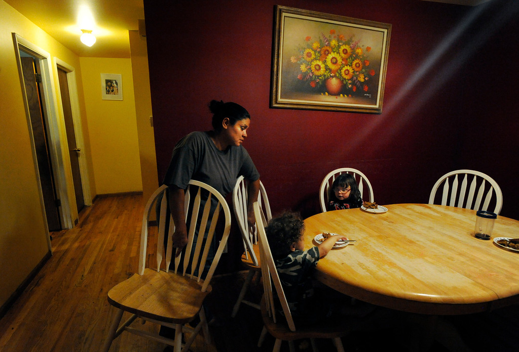 . Ena picks up dining room chairs, which are kept in a closed room, so the family\'s two cats can eat in peace on the table during the day and through the night. Ena and Brent Batron are both blind, and raising their five kids under the age of 10.  Photo by Jamie Cotten, Special to The Denver Post