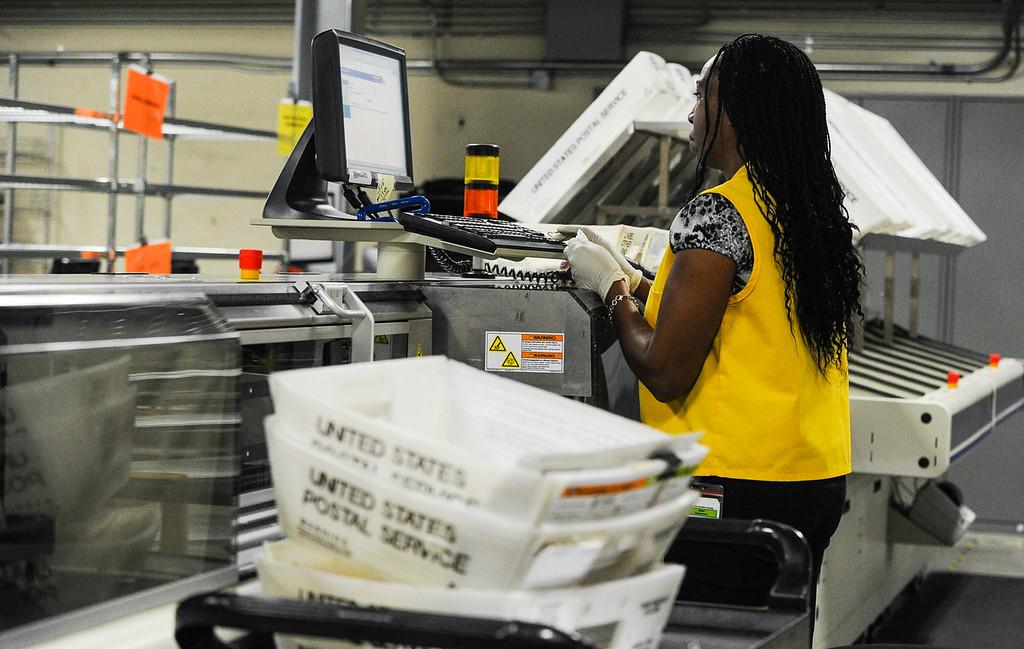 . Mail ballot processing team employee Alondra Lucious processes mail-in ballets at the Registrar of Voters office in San Bernardino on Monday, Nov. 4, 2013. (Photo by Rachel Luna / San Bernardino Sun)