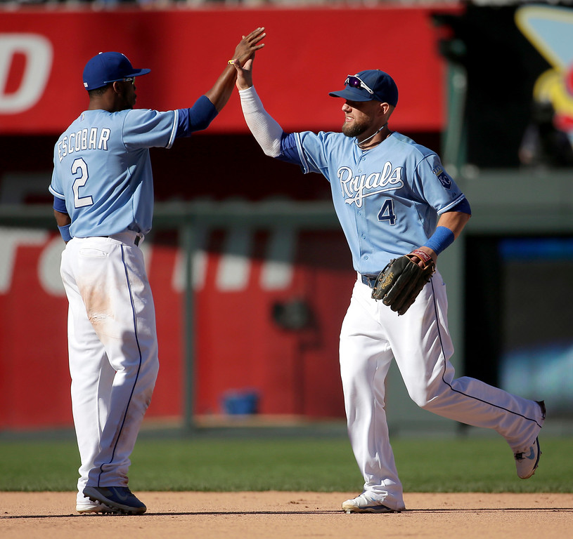 . Kansas City Royals\' Alex Gordon (4) and Alcides Escobar (2) celebrate after their baseball game against the Detroit Tigers, Sunday, Sept. 21, 2014, in Kansas City, Mo. The Royals won 5-2. (AP Photo/Charlie Riedel)