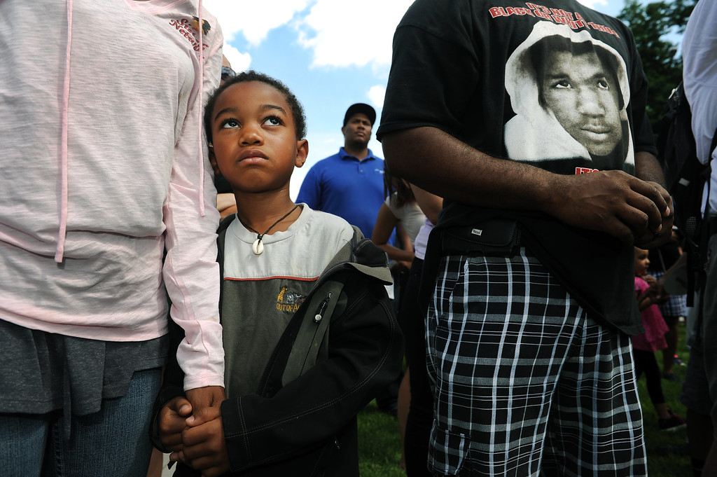 """. Simba Jones holds the hand of his mother Phoenix Jones, left hands during the rally in City Park in Denver, CO on July 14, 2013.  Several hundred people turned out  to show their disappointment in the acquittal of George Zimmerman in the murder trail of Trayvon Martin.  Zimmerman is the Florida man who shot and killed Trayvon Martin. \""""We will not erase the conversation of race,\"""" said Jeff Fard, founder of Brother Jeff\'s Cultural Center in the Five Points neighborhood. \""""Don\'t be afraid to say if Trayvon Martin was a white man he would be alive today.\""""  Photo by Helen H. Richardson/The Denver Post)"""