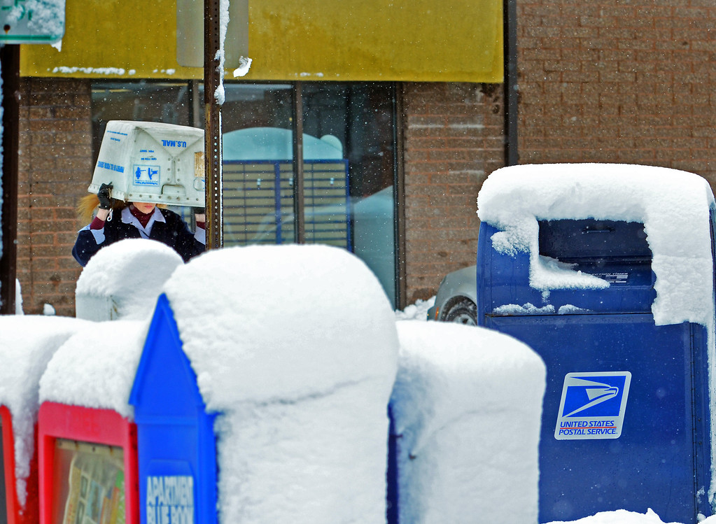 . Clerk Lisa Esherman shields herself from snow as she heads out  to collect mail from outdoor mailboxes at the Lansdale Post Office.   Monday,  February 3, 2014.  Photo by Geoff Patton