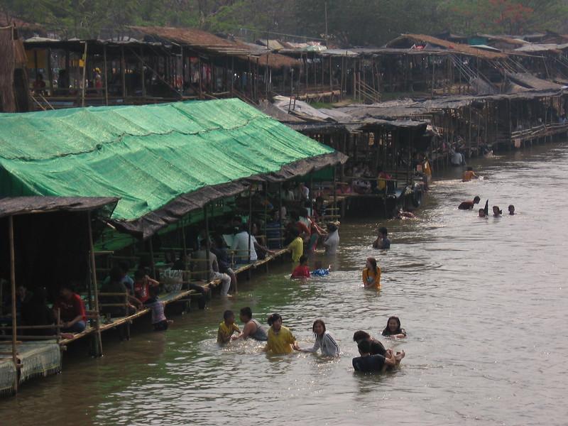 Locals enjoy eating/drinking in bamboo huts along the Mae Kok River at Chiang Rai Beach.