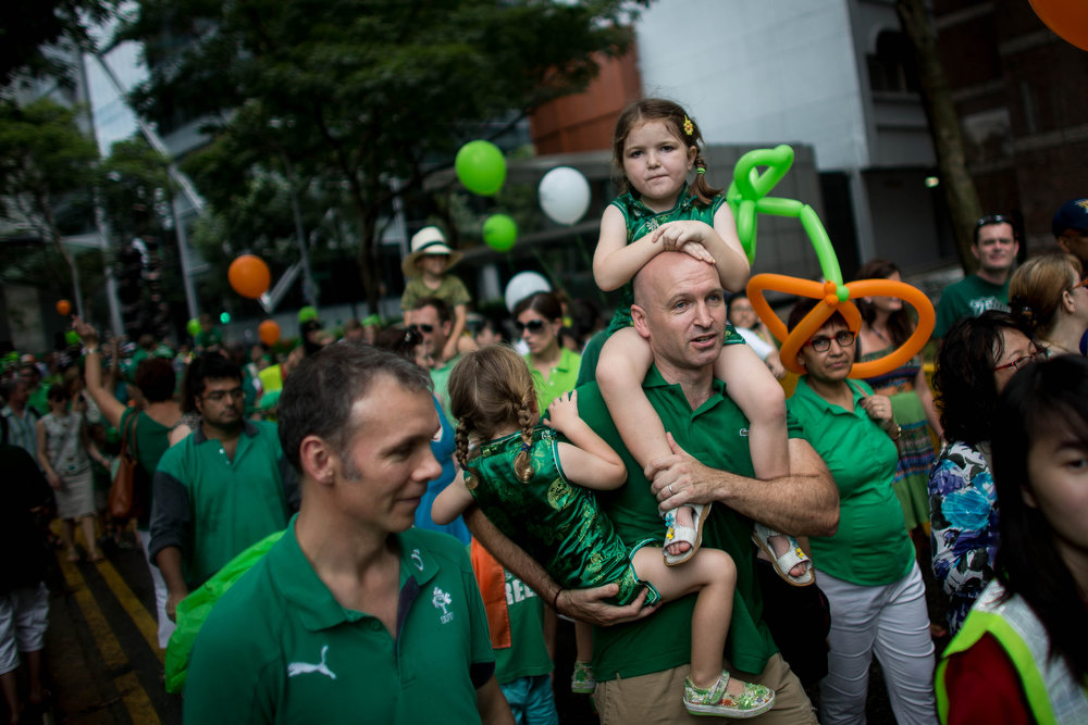. A man carries children down the street during the St. Patricks Day Parade at Boat Quay on March 17, 2013 in Singapore.  Singapore\'s Irish community gathered at Boat Quay for a three-day-long St. Patrick\'s Day Street Festival which featured street performances, buskers, and Irish food and drink.  (Photo by Chris McGrath/Getty Images)