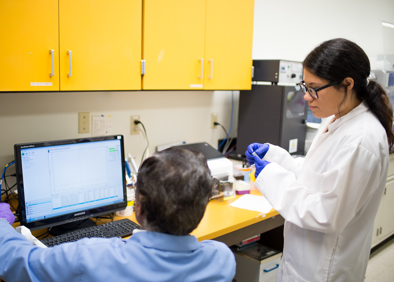 Student Anali Martinez listens to her lab professor explain DNA extraction in a Biochemistry lab.