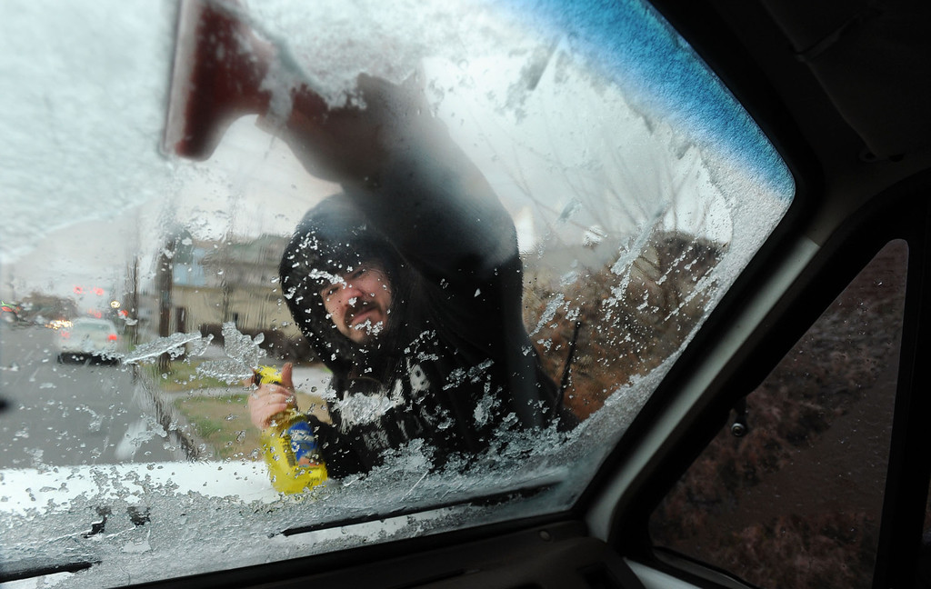 . Seth English scraps the ice off his car windshield Friday, Dec. 6, 2013 in Owensboro, Ky. Kentucky Transportation Cabinet maintenance crews were out treating roadways early Friday in anticipation of the winter weather, and multiple school districts called off classes.  (AP Photo/The Messenger-Inquirer, John Dunham )