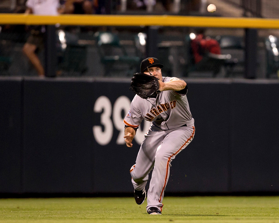 . DENVER, CO - AUGUST 27:  Left fielder Roger Kieschnick #22 of the San Francisco Giants makes a catch on the run for the first out of the fourth inning against the Colorado Rockies at Coors Field on August 27, 2013 in Denver, Colorado.  The Giants defeated the Rockies 5-3.  (Photo by Justin Edmonds/Getty Images)