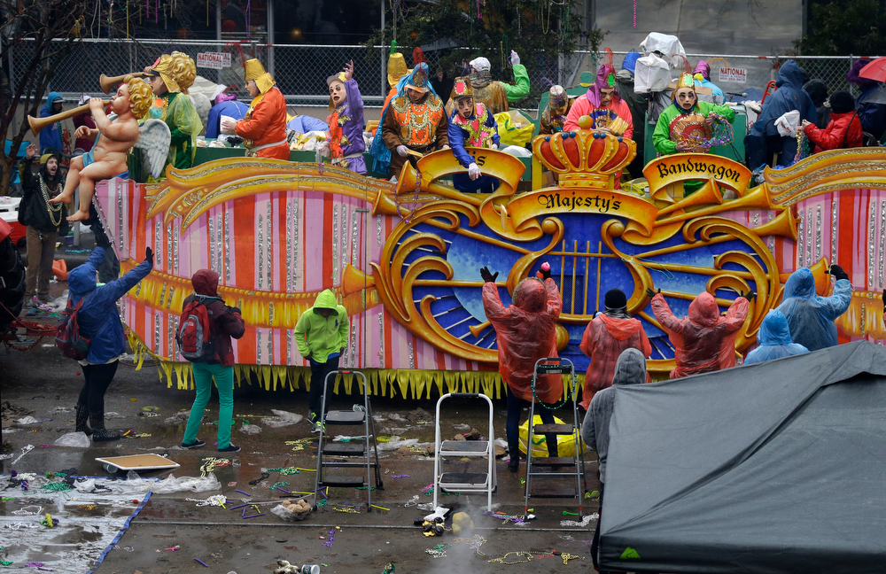 Description of . Members of the Krewe of Rex, throw beads and trinkets from a float along a largely empty St. Charles Ave., during Mardi Gras in New Orleans, Tuesday, March 4, 2014. Rain and cold temperatures kept the normally massive and festive crowds away. (AP Photo/Gerald Herbert)