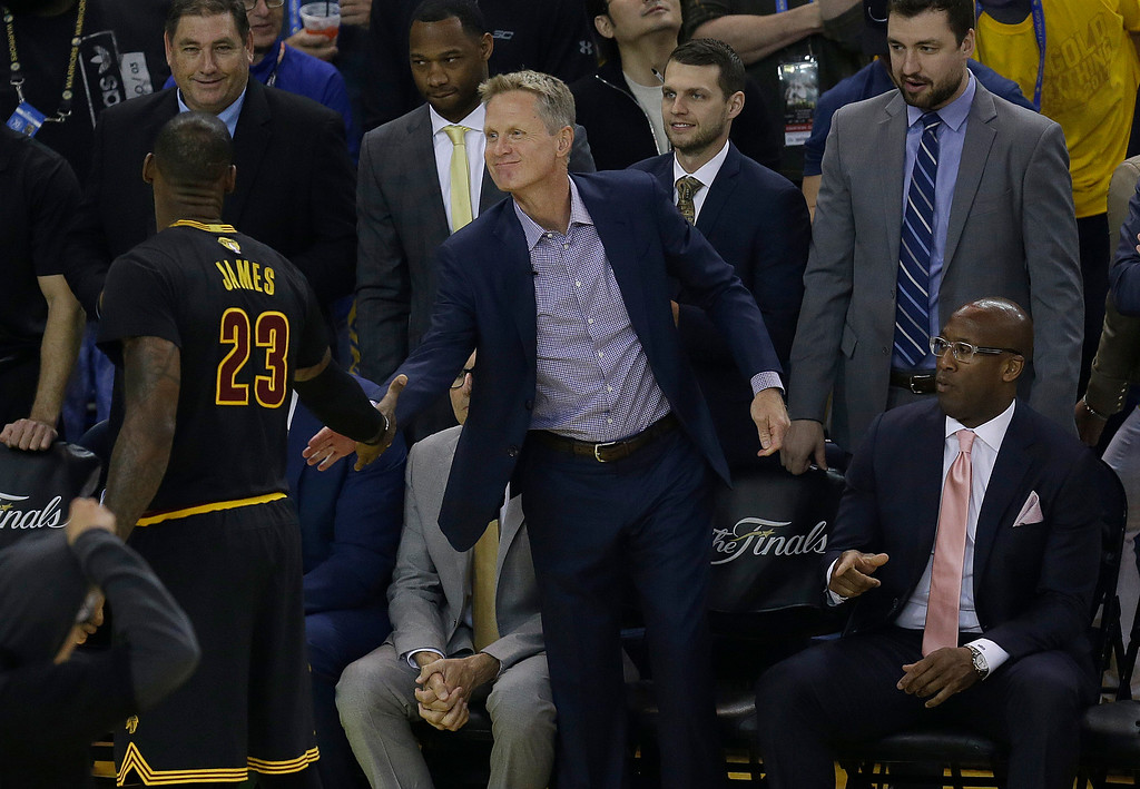 . Cleveland Cavaliers forward LeBron James (23) shakes hands with Golden State Warriors head coach Steve Kerr as Mike Brown, bottom right, watches before Game 2 of basketball\'s NBA Finals between the Warriors and the Cavaliers in Oakland, Calif., Sunday, June 4, 2017. (AP Photo/Ben Margot)