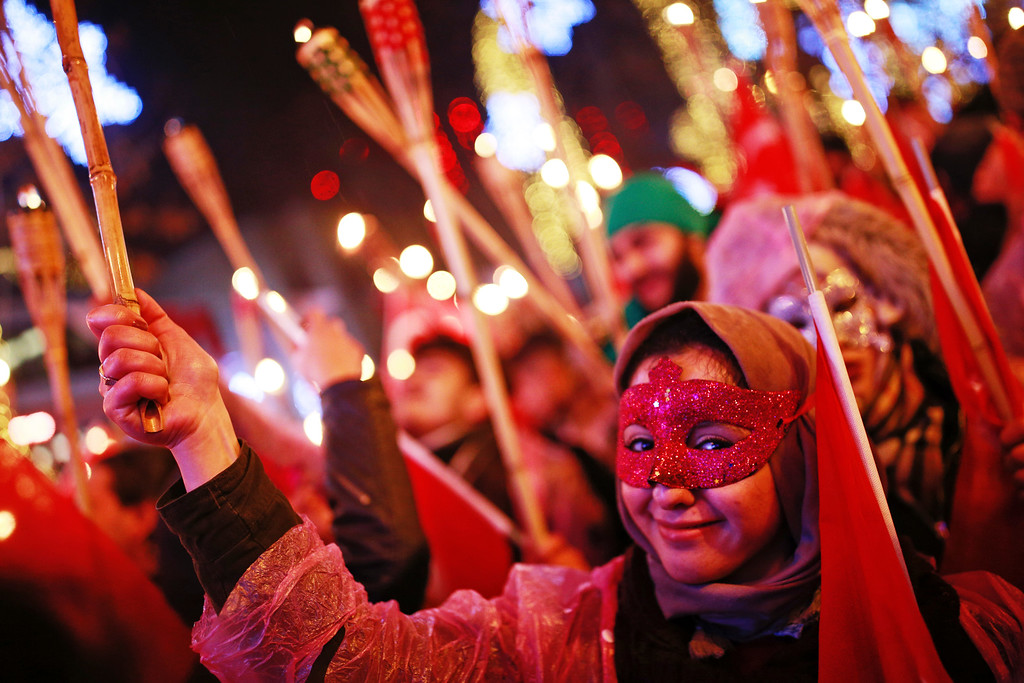 . People hold torches during New Year\'s cerebrations in Istanbul\'s Ortakoy district by the Bosphorus, during New Year\'s cerebrations, late Saturday, Dec. 31, 2016. (AP Photo/Emrah Gurel)