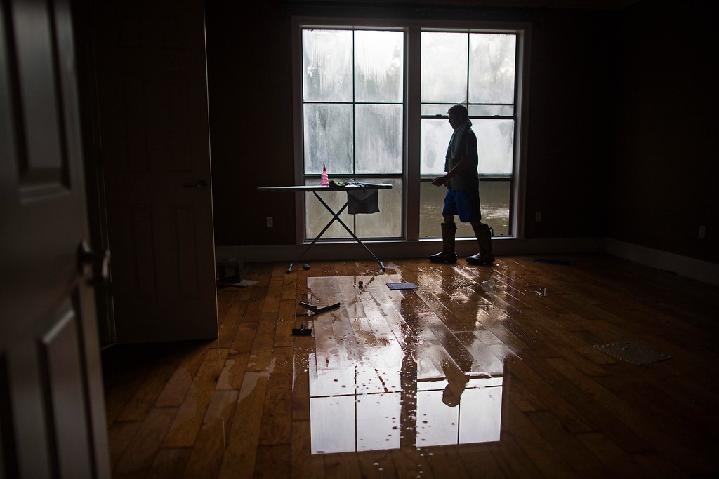 . David Key opens the windows in his flooded home in Prairieville, La., Tuesday, Aug. 16, 2016. Key, an insurance adjuster, fled his home as the flood water was rising with his wife and three children and returned today to assess the damage. (AP Photo/Max Becherer)