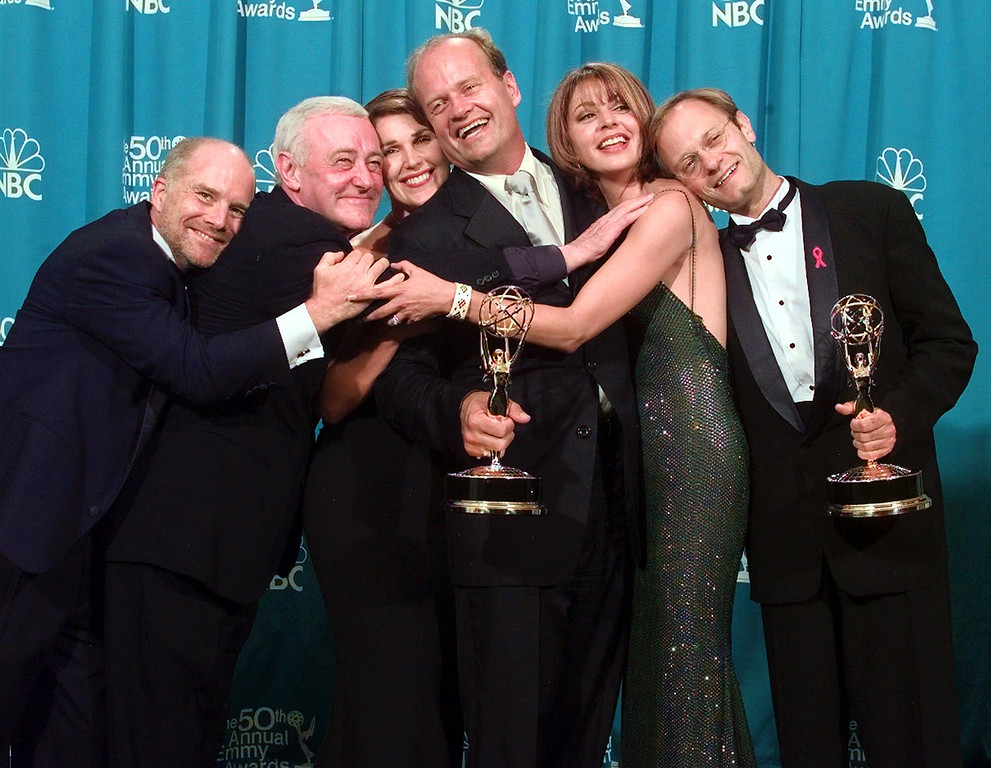 """. Cast members of \""""Frasier,\"""" winner of the Emmy for Outstanding Comedy Series, have a group hug backstage  at the 50th Annual Primetime Emmy Awards at the Shrine Auditorium in Los Angeles, Sunday, Sept. 13, 1998. From left are Dan Butler, John Mahoney, Peri Gilpin, Kelsey Grammer, Jane Leeves and David Hyde Pierce. Grammer and Pierce also won Emmys. (AP Photo/Reed Saxon)"""