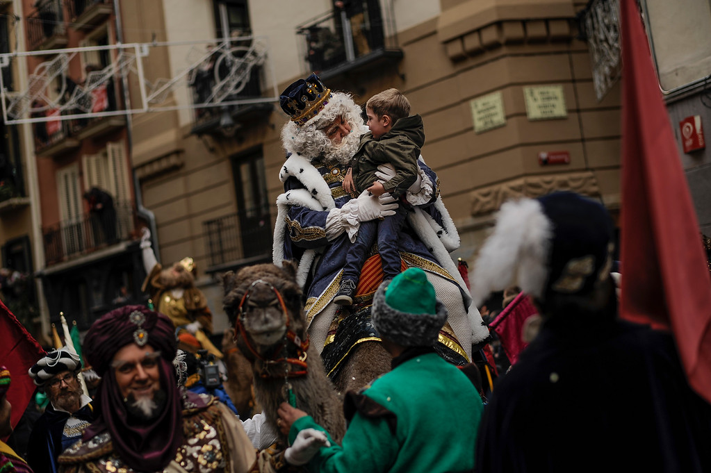 . One king of The Cabalgata Los Reyes Magos (Cavalcade of the three kings) holds a boy during the cavalcade the day before Epiphany, in Pamplona, northern Spain, Tuesday, Jan. 5, 2016. It is a parade symbolizing the coming of the Magi to Bethlehem following the birth of Jesus. In Spain and many Latin American countries Epiphany is the day when gifts are exchanged. (AP Photo/Alvaro Barrientos)