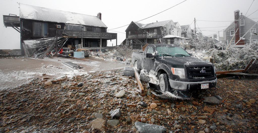 . Damaged houses and a truck sit along the coast in the Brant Rock section of Marshfield, Mass., during a winter snowstorm Tuesday, Jan. 27, 2015. Two feet of snow or more was expected in most of Massachusetts by the end of the storm. (AP Photo/The Patriot Ledger, Greg Derr)