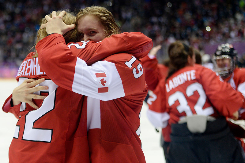 . SOCHI, RUSSIA - FEBRUARY 20: Hayley Wickenheiser (22) of the Canada and Brianne Jenner (19) hug as team Canada celebrates the game-winning goal by Marie-Philip Poulin (29) during the overtime period of Canada\'s 3-2 gold medal ice hockey win over the U.S.A. Sochi 2014 Winter Olympics on Thursday, February 20, 2014 at Bolshoy Ice Arena. (Photo by AAron Ontiveroz/ The Denver Post)