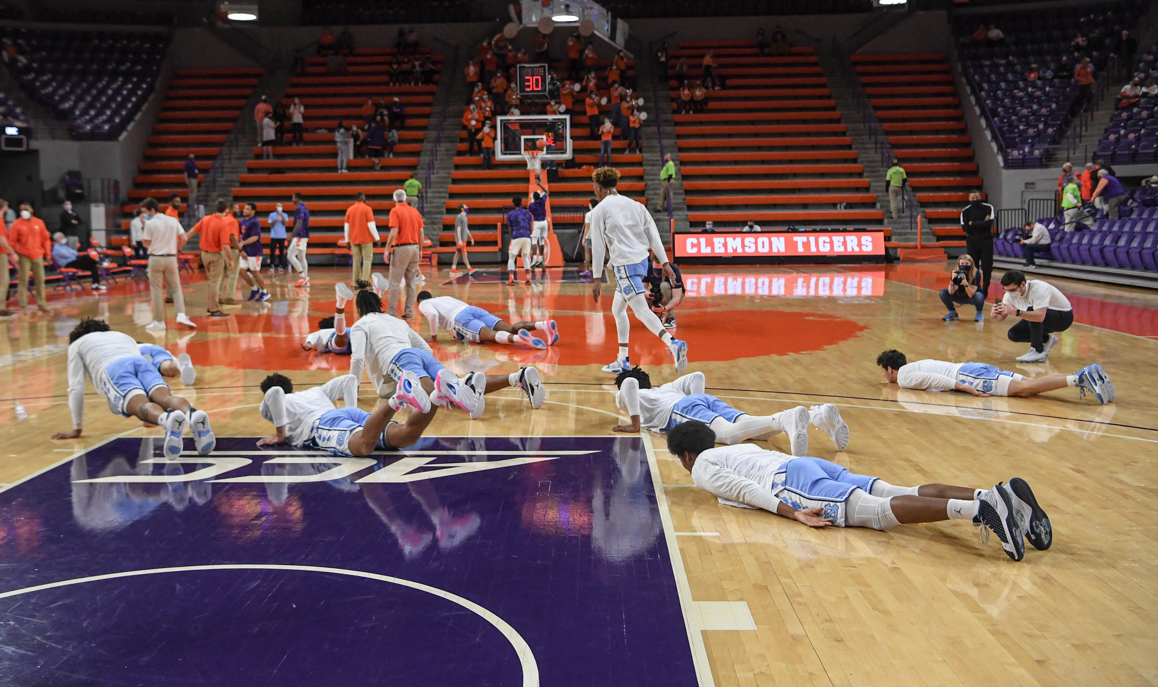North Carolina players lay down on the floor after warmups before tipoff with Clemson Feb 2, 2021; Clemson, South Carolina, USA;  at Littlejohn Coliseum.