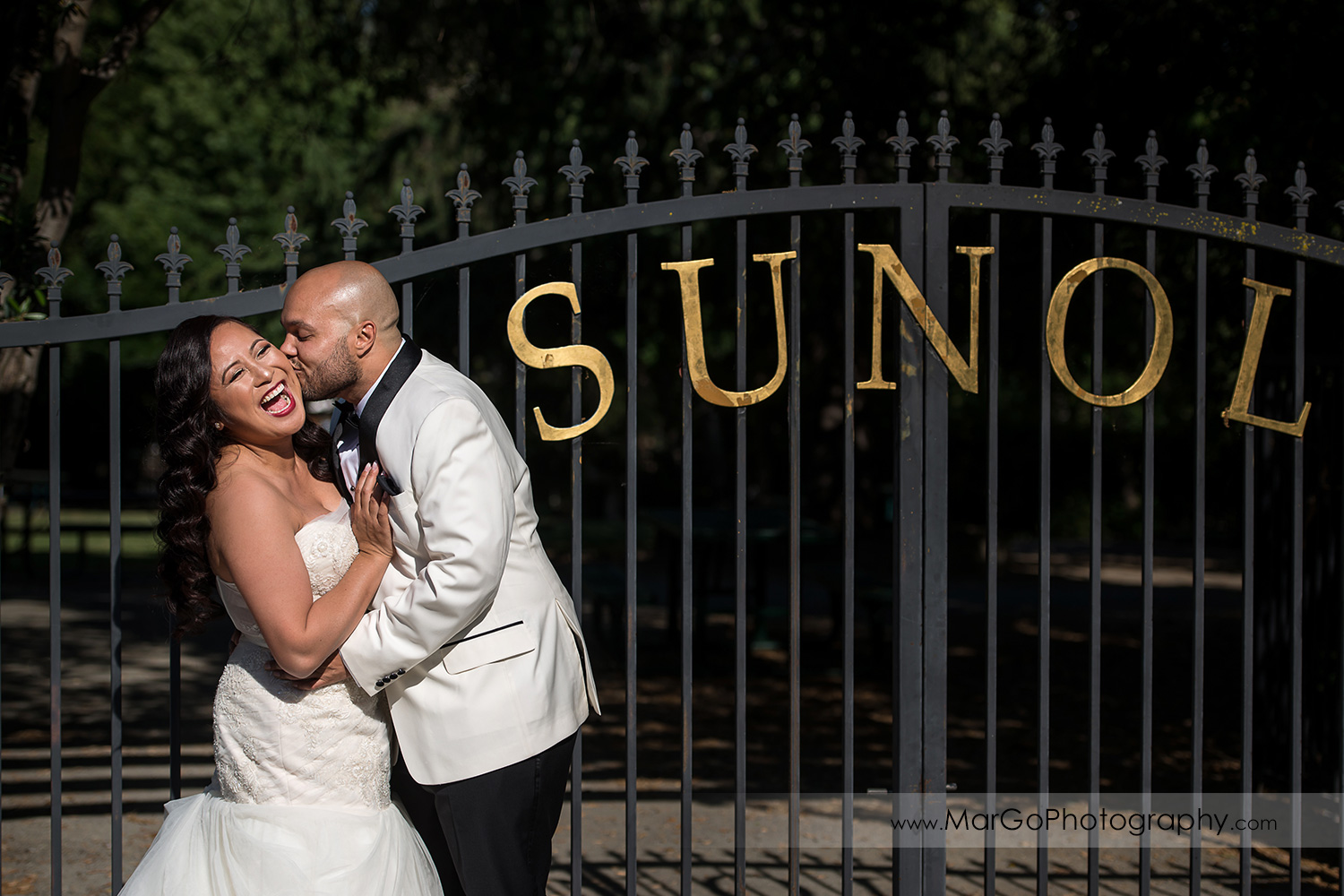bride and groom laughing in front of park gate near Sunol's Casa Bella