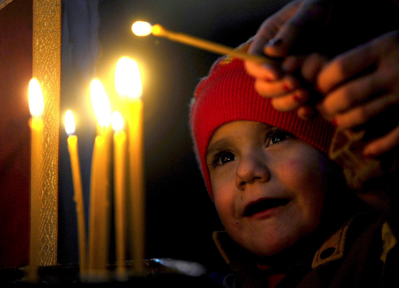 . A boy lights a candle, during a Christmas service in the Christian Orthodox church,  St. Atanasij the Great, in the southeastern Macedonia\'s town of Bogdanci, on Monday, Jan. 7, 2013. Orthodox Christians celebrate Christmas day on January 7 because they follow the Julian Calendar, which was replaced in Western Europe by the Gregorian calendar 500 years ago. (AP Photo/Boris Grdanoski)