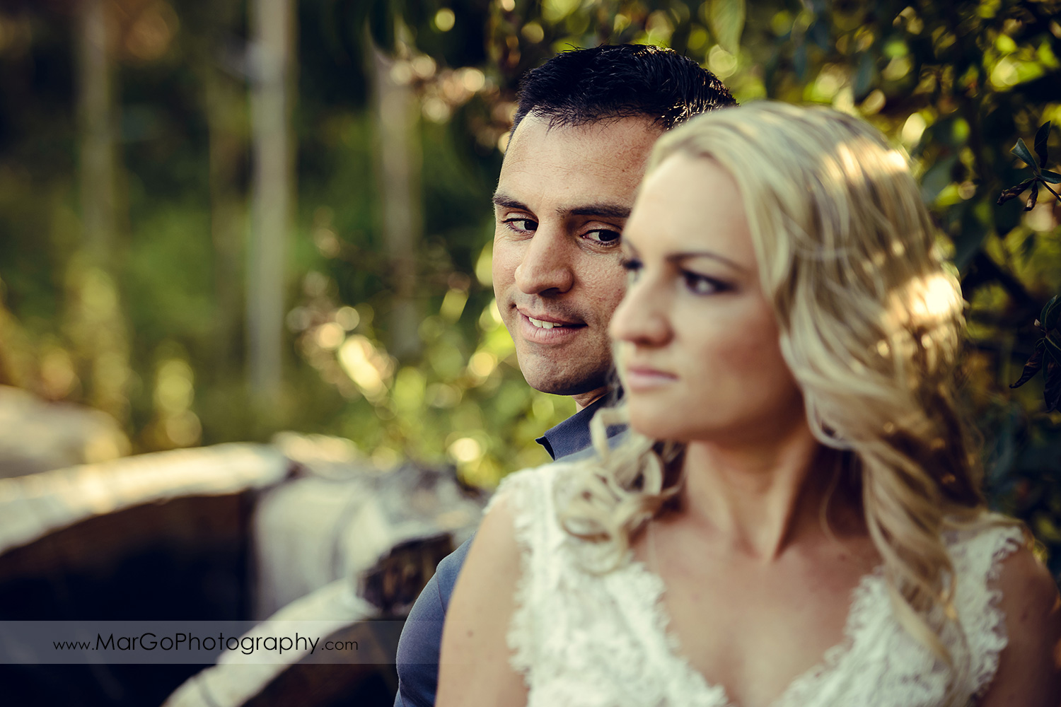 portrait of man in navy blue shirt through woman in white dress sitting back to back during engagement session at San Francisco Golden Gate Park