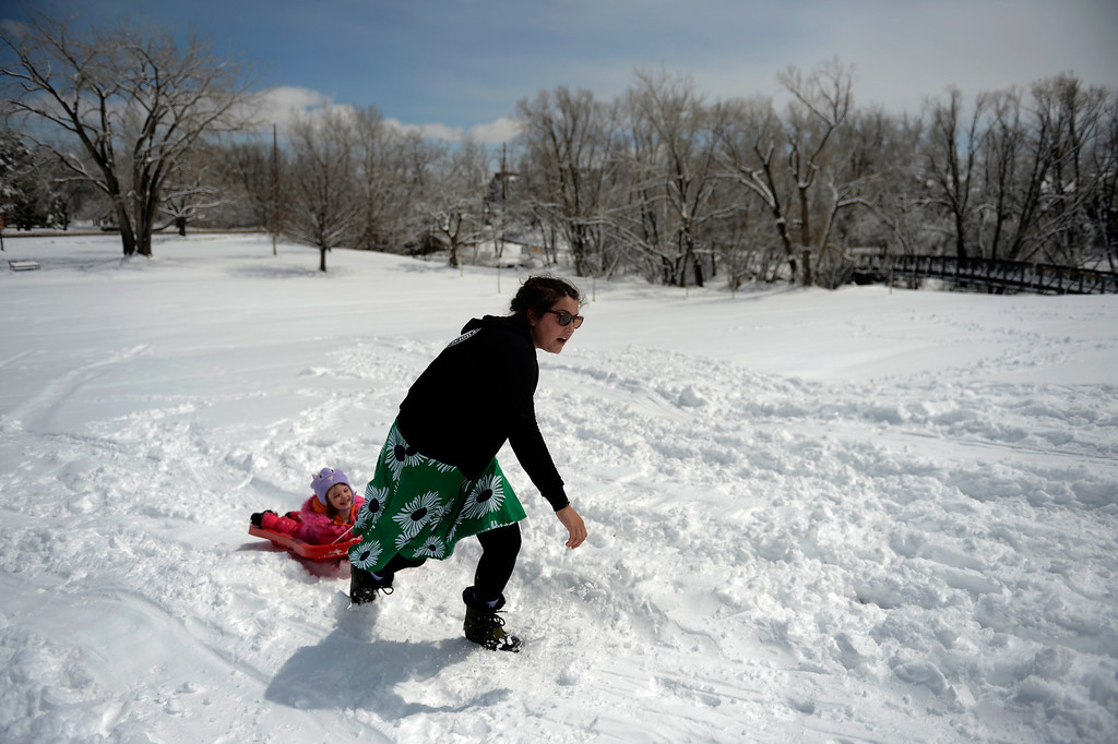 . BOULDER, CO. - APRIL 23: 4 year old Megan Doyle is pulled up the hill by her mom Lily as they sleds at Scott Carpenter Park April 23, 2013 Boulder, Colorado. (Photo By Joe Amon/The Denver Post)