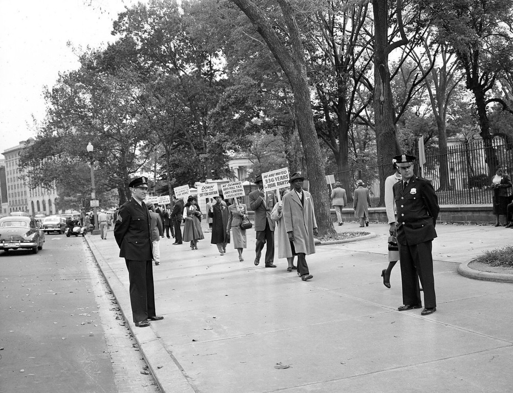 . Officers stands by as black religious leaders from Chicago demonstrate outside the White House in Washington against the murder of 14-year-old Chicagoan boy Emmett Louis Till, on October 24, 1955.  (AP Photo)