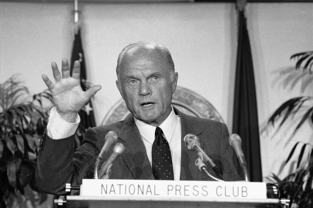 ". Sen. John Glenn, D-Ohio, addresses a meeting of the National Press Club, Wednesday, Oct. 13, 1983 in Washington. Following the speech Glenn told reporters Walter Mondale\'s recent attack on his Reaganomics voting record could help ""give the President a free ride\"" to re-election over both of the Democratic contenders. (AP Photo/Ira Schwarz)"