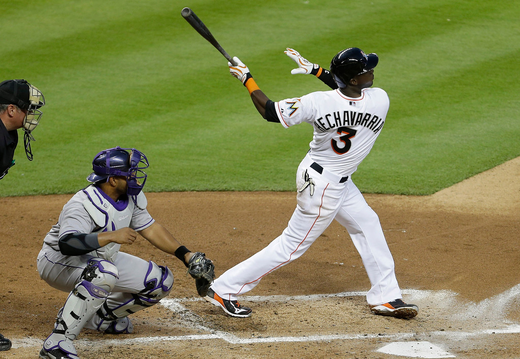 . Miami Marlins\' Adeiny Hechavarria (3) hits a sacrifice fly to score Jarrod Saltalamacchia as Colorado Rockies catcher Wilin Rosario, left, looks on in the third inning of a baseball game against the Colorado Rockies, Tuesday, April 1, 2014, in Miami. The Marlins defeated the Rockies 4-3. (AP Photo/Lynne Sladky)