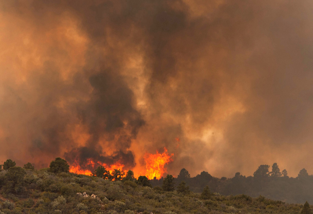 . Flames top a ridge as the Yarnell Hill Fire moves towards Peeples Valley, Arizona on Sunday, June 30, 2013. (AP Photo/The Arizona Republic, Tom Story)