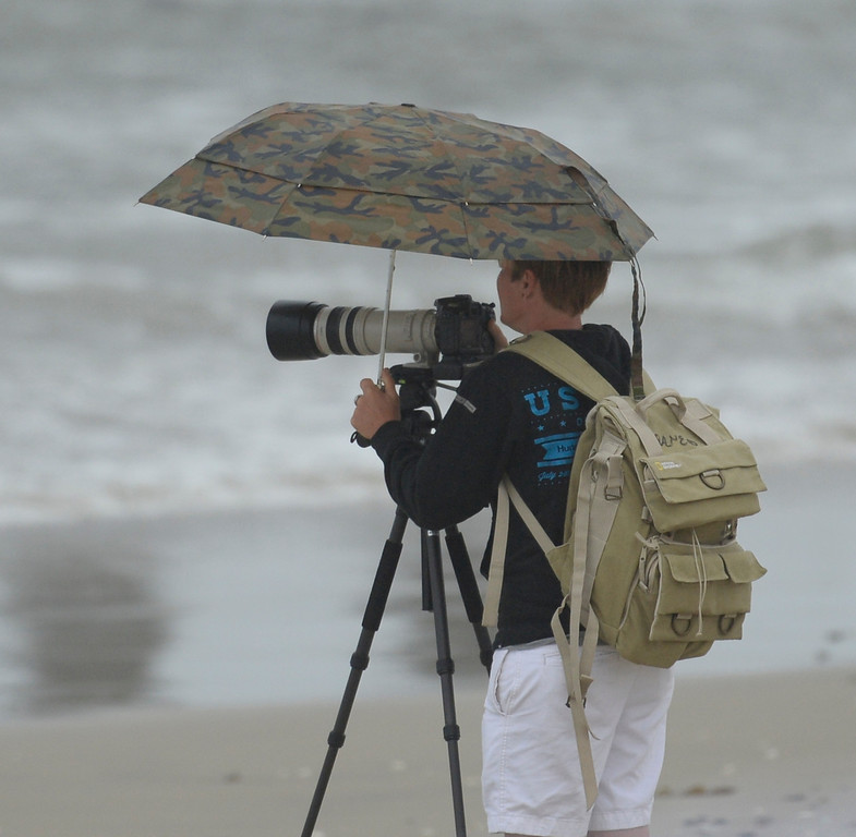 . Photographers do what they can to keep the cameras dry  during the 2013 Vans US Open of Surfing Sunday at Huntington Beach CA. July 27,2013. Photo by Gene Blevins/LA DailyNews
