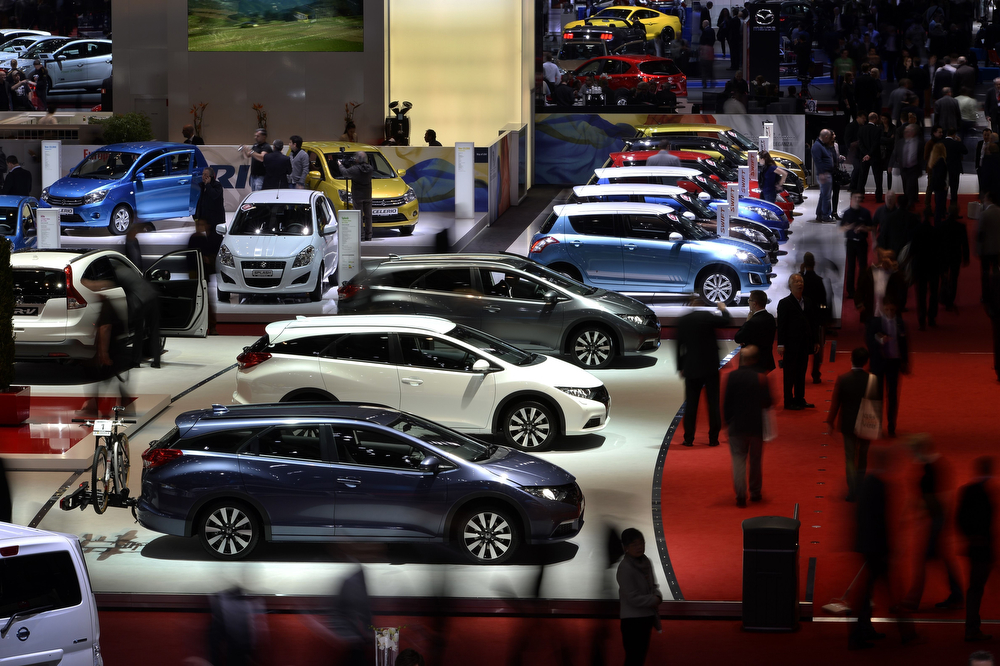 . People attend the press day of the Geneva Motor Show in Geneva, on March 5, 2014. Automobile giants pitched smaller, nimbler cars to tempt cash-strapped consumers in a recovering European market, with compact vehicles taking centre stage at the Geneva Motor Show. (FABRICE COFFRINI/AFP/Getty Images)