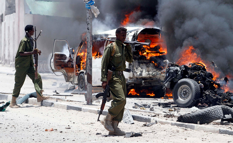 . Policemen walk past the scene of an explosion near the presidential palace in Somalia\'s capital Mogadishu, March 18, 2013. A car bomb exploded near the presidential palace in the Somali capital Mogadishu on Monday, killing at least 10 people in a blast that appeared to target senior government officials, police said. REUTERS/Feisal Omar