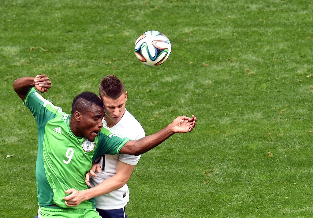 . Nigeria\'s forward Emmanuel Emenike (L) and France\'s defender Laurent Koscielny clash during a Round of 16 football match between France and Nigeria at Mane Garrincha National Stadium in Brasilia during the 2014 FIFA World Cup on June 30, 2014.   EVARISTO SA/AFP/Getty Images