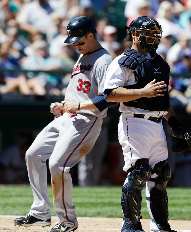. Minnesota Twins\' Justin Morneau scores as Seattle Mariners catcher Humberto Quintero stands by in the fourth inning. (AP Photo/Elaine Thompson)