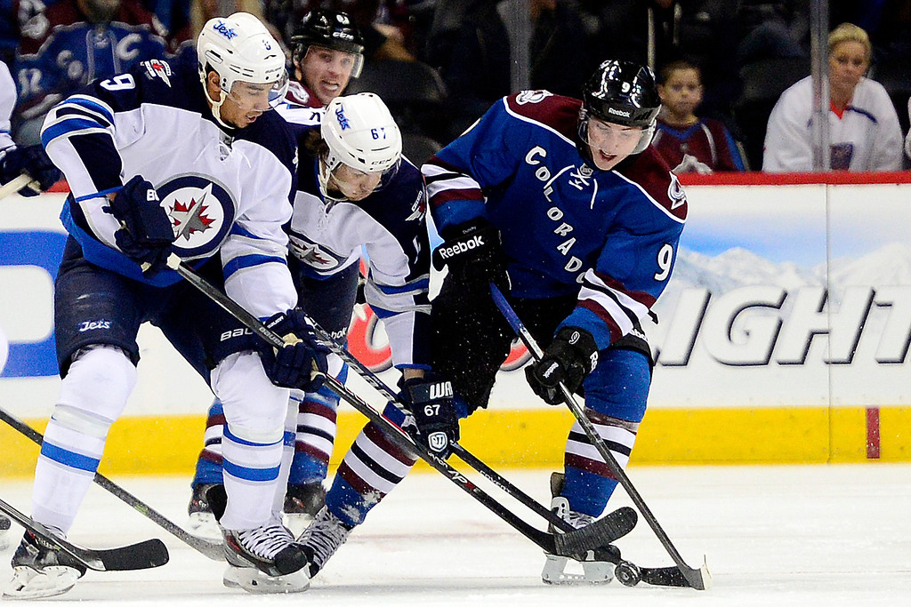 . Matt Duchene (9) of the Colorado Avalanche controls the puck as Evander Kane (9) of the Winnipeg Jets and Michael Frolik (67) of the Winnipeg Jets defend during the first period of action.   (Photo by AAron Ontiveroz/The Denver Post)
