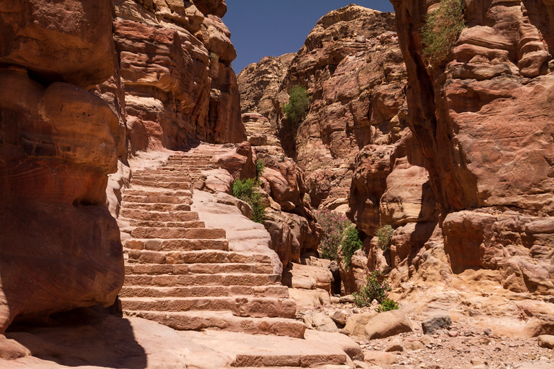 stairs carved into the desert lead to more ancient buildings in Petra, Jordan
