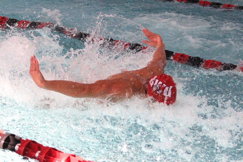 Swimmers compete in the butterfly.
