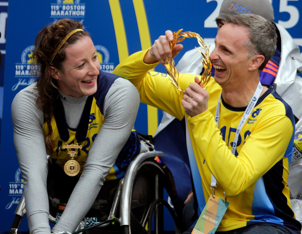 . Bill Richard, right, father of 2013 Boston Marathon bombing victim Martin Richard, prepares to put the victor\'s wreath on women\'s wheelchair division winner Tatyana McFadden, of Russia, at the Boston Marathon, Monday, April 20, 2015 in Boston. (AP Photo/Charles Krupa)