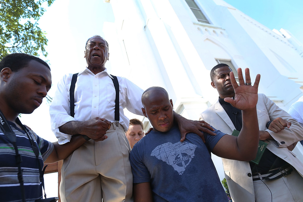 . Rev. Franklin Ferguson (2nd L) and Pastor Philip Pinckney (2nd R) join together to lead a group prayer in front of the Emanuel African Methodist Episcopal Church after a mass shooting at the church killed nine people on June 20, 2015 in Charleston, South Carolina. Suspect Dylann Roof, 21, was arrested and charged in the killing of nine people during a prayer meeting in the church, one of the nation\'s oldest black churches in the South.  (Photo by Joe Raedle/Getty Images)