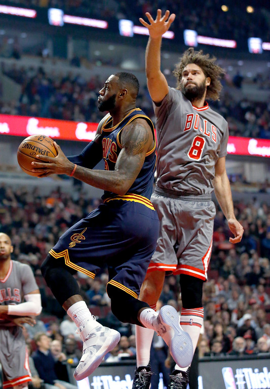 . Cleveland Cavaliers forward LeBron James, left, drives to the basket past Chicago Bulls center Robin Lopez during the first half of an NBA basketball game Friday, Dec. 2, 2016, in Chicago. (AP Photo/Nam Y. Huh)