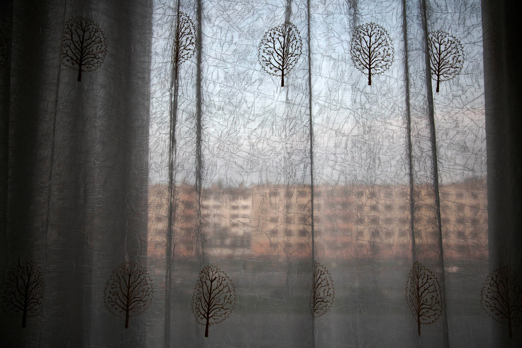 """. In this June 15, 2014 photo, an apartment block stands behind hotel room curtains on the main street in Hamhung, North Korea. The Associated Press was granted permission to embark on a weeklong road trip across North Korea to the countryís spiritual summit Mount Paektu. The trip was on North Korea\'s terms.  An AP reporter and photographer couldn\'t interview ordinary people or wander off course, and government \""""minders\"""" accompanied them the entire way. (AP Photo/David Guttenfelder)"""