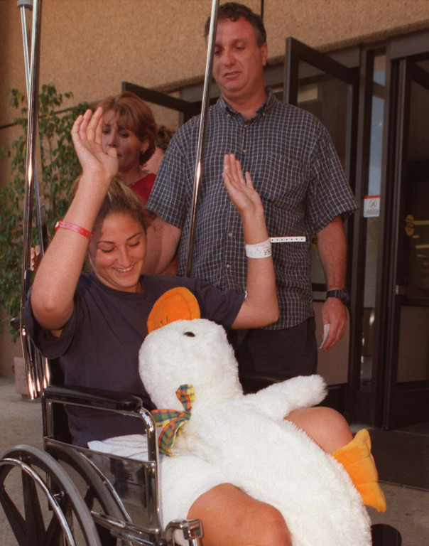 . Mindy Finkelstein, along with father Dave Finkelstein and mother Donna Finkelstein, raises her hands in response to how she is felling after leaving Kaiser Permanente Hospital in Woodland Hills, Thursday August 12.   Los Angeles Daily News file photo.