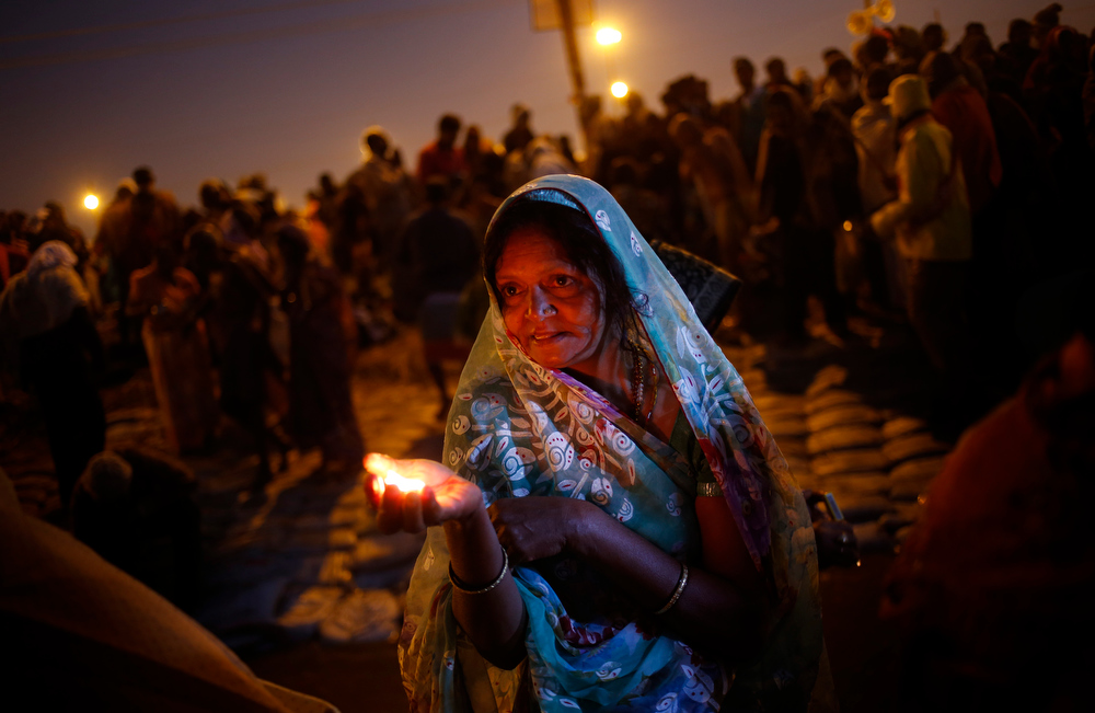 Description of . A Hindu devotee lights a lamp to worship the river Ganges at