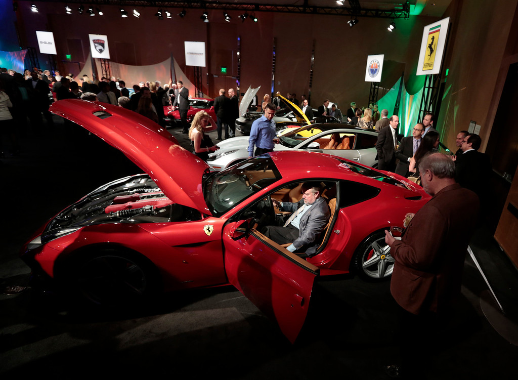 . An attendee sits inside a red Ferrari SpA F12 at The Gallery in the MGM Grand Detroit ahead of the 2013 North American International Auto Show (NAIAS) in Detroit, Michigan, U.S., on Saturday, Jan. 12, 2013. The Detroit auto show runs through Jan. 27 and will display over 500 vehicles, representing the most innovative designs in the world. Photographer: Jeff Kowalsky/Bloomberg